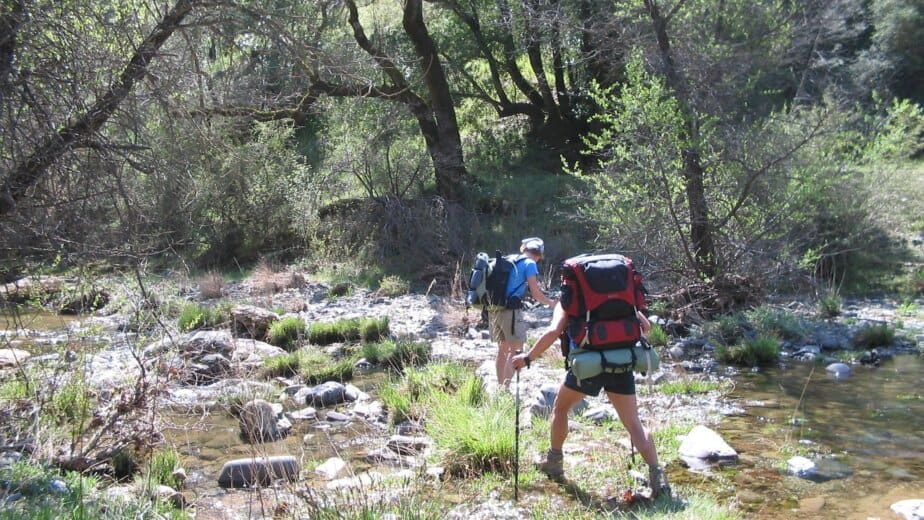 backpacking crossing a river